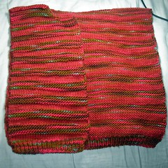 Photo of right front of Christmas Spices Cardigan, laid over back of cardigan, knit in alternating stockinette stitch and garter stitch.  Stockinette stitch is knit in semi-solid burgundy wool (Galenas Merino in Cinnamon Spices colorway).  Garter stitch is knit in variegated red, burgundy, brown, light blue, and olive green wool (Galenas Merino in Gingerbread House colorway).  Cardigan is Lion Brand's Striped Cardi pattern in size 5T.