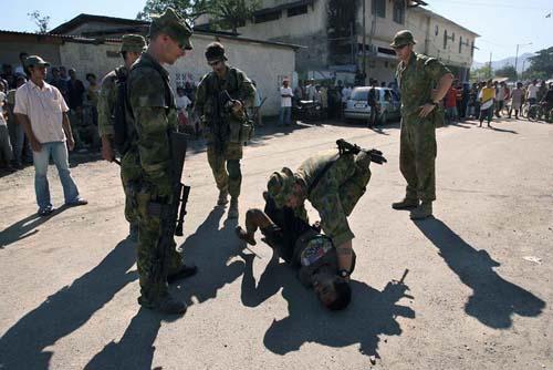 Tentara Australia menangkap seorang warga yang membawa pisau saat antri beras di gudang pemerintah di Bebora, Dili.