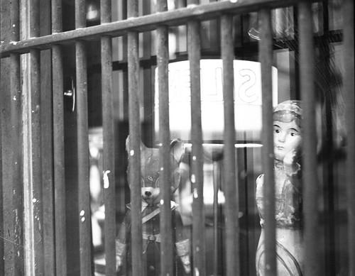 En ce promenant dans le vieux quartier, il était tombé en arrêt devant cette vitrine protégée d'épais barreaux et le pantin triste qu'elle abritait