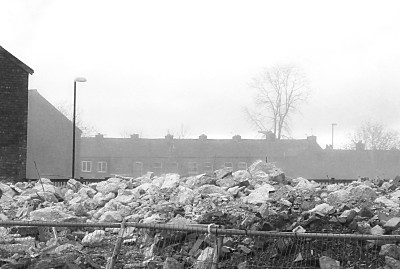 looking across the demolished DSS building to the houses behind, almost obscured by the smoke drifting across still.