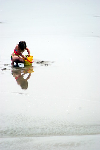Child at the beach filling a bucket