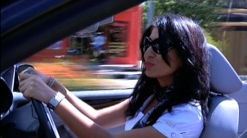 INTERIOR SHOT: Protagonist of the movie, driving a sportscar. Background is blurred due to motion of car. Protagonist is a dressed in white blouse with black cravat, wearing makeup, sunglasses and expensive jewelry.