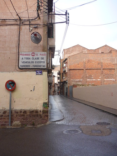 A street with many derelict buildings in a village in Spain
