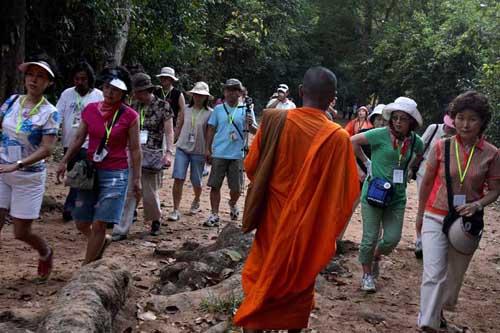 Pheakhdey berjalan melewati rombongan turis asal Korea yang berkunjung ke Angkor Wat di Siem Reap, Kamboja.