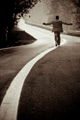 image of a man standing in the middle of a road with his hands held out
