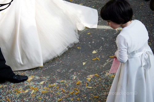 A flower girl looks at the rice and pasta at the Italian bridal couple's feet