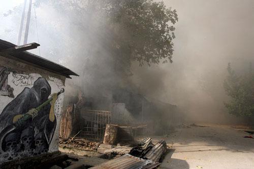 Warga masih terus membakari rumah-rumah dipinggiran kota Dili setelah dua minggu kerusuhan yang disebabkan krisis politik di Timor Leste. Foto-foto ini bagian dari liputan konflik saudara di Timor Leste akibat krisis politik yang menimbulkan kesengsaraan bagi warga Timor itu sendiri. Orang Loro Sae (Timor bagian timur) baku bunuh dengan orang Loro Munu (Timor bagian barat), rumah-rumah dibakar, warga mengungsi. Merekapun  mulai menjarah gudang-gudang beras milik pemerintah karena bahan makanan mulai sulit didapatkan, kemudian membuat tentara Australia yang bertanggungjawab atas keamanan mengatur antrian untuk membagikan beras kepada penduduk.
