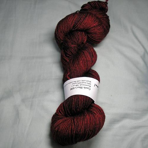 Photo of skein of Castle Fibers sock yarn in semi-solid dark red