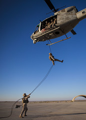 A U.S. Marine rappels from a UH-1N Huey helico...