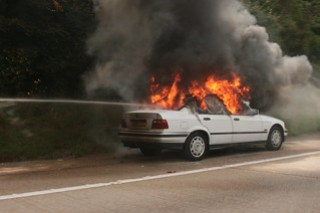 White sedan in flames at side of the road; jet of water from unseen hose blasting through back window.