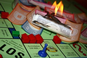 Burning money on a Monopoly board.