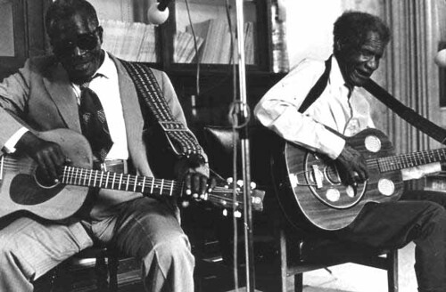 """Rev. N.L. Williams playing blues guitar while """"Blind"""" Johnny Brown plays a resonator guitar"""