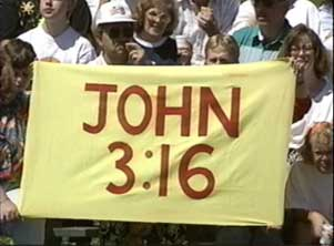 "A sign reading ""John 3:16"" held up in a crowd"