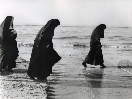 Pootjebadende nonnen op het strand / wading nuns
