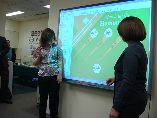 """Demonstrating a teaching game made with the SMART Board software. """"SMARTBoard Showcase 014"""" by Lisa Thumann from Flickr Creative Commons."""