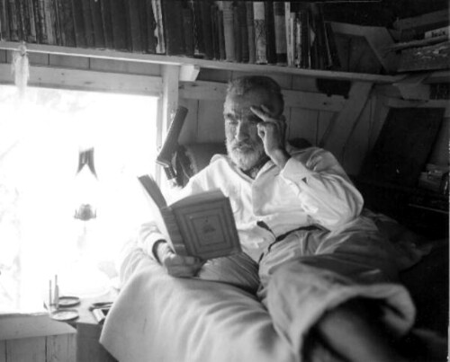 Old hermit Roy Ozmer reading a book at his house: Pelican Key, Florida