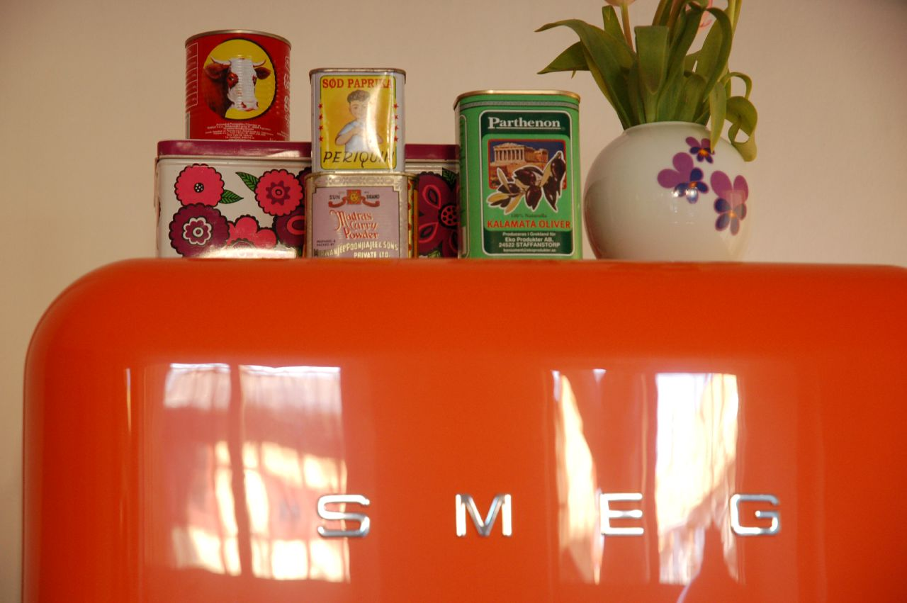 Orange smeg 50 style fridge with tins