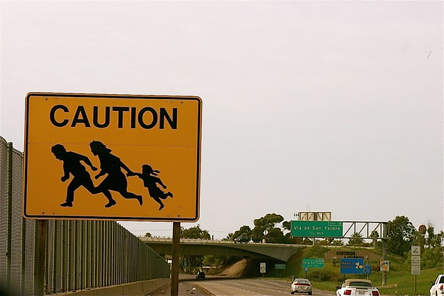 """Photo of a """"Caution"""" sign by the side of a highway next to a very tall border wall. The """"Caution"""" sign has a picture of a man, woman and child running"""
