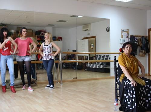 Alumnas ensayando una de las escenas de la obra. En el centro hay una mujer sentada en una silla vestida de gitana, detrás de ella, a unos metros, se encuentran tres alumnas mirándola y riéndose de esta primera