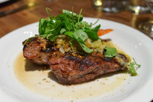 Grilled Pork Chop, Carrots, Sauerkraut, Golden Raisins and Mustard Vinaigrette