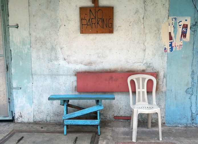 no parking sign above a monobloc chair and a blue bench