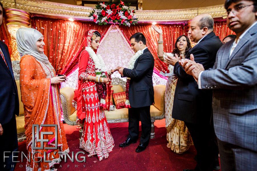 Bride and groom exchange rings during Muslim wedding
