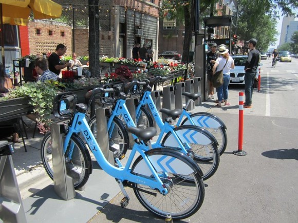 three people wait in line at a Divvy station