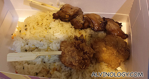 A box of rice with two skewers
