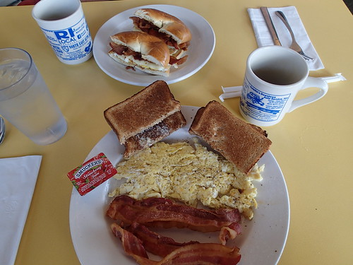 Scrambled eggs, bacon, wheat toast with strawberry jam, and on his plate, bacon/egg/cheese on a bagel, all washed down with good diner coffee