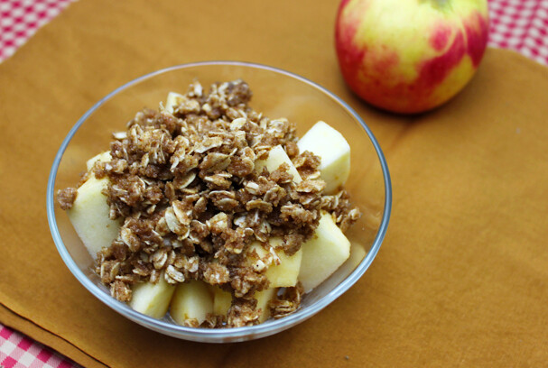 Small glass bowl of chopped apples topped with an oat-y crumble with a whole apple to the side.