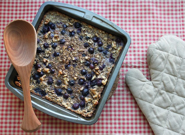 Top-down view of a metal baking dish filled with a casserole-like baked oatmeal studded with blueberries. To the right is a tan baking mitt, and across the top of the dish is a wooden spoon.