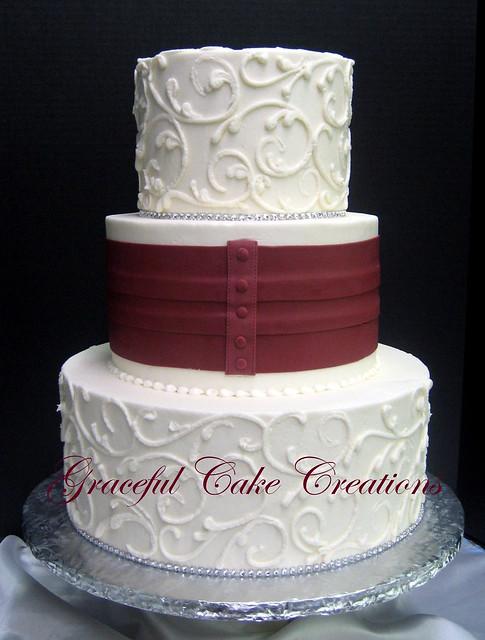 Elegant Ivory Wedding Cake With A Burgundy Sash And Bow