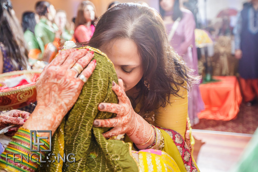 Groom's mother throwing rose petals on bride during Pithi ceremony