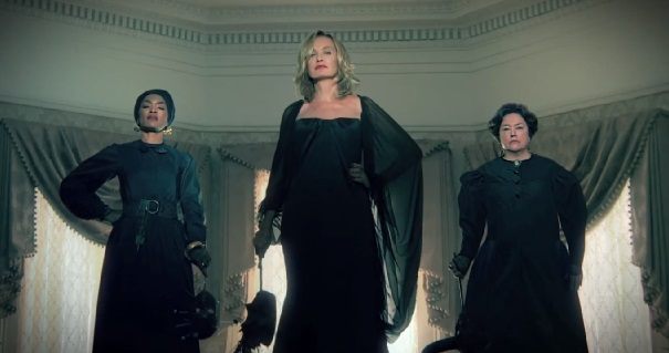 Jessica Lange stands in the middle of three witches dressed in black
