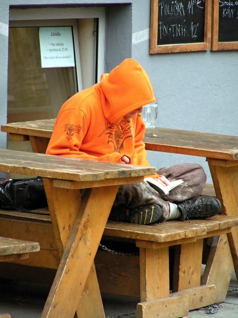 Reading Man in Orange Hoodie