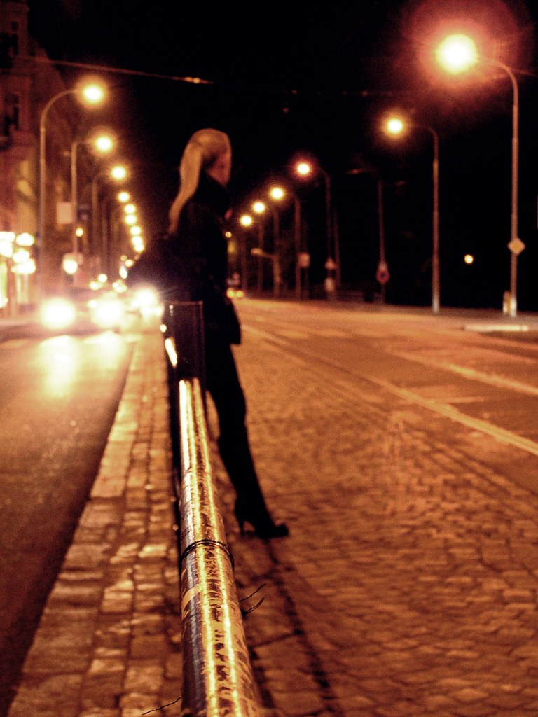 Young Woman Waiting for a Tram at Night