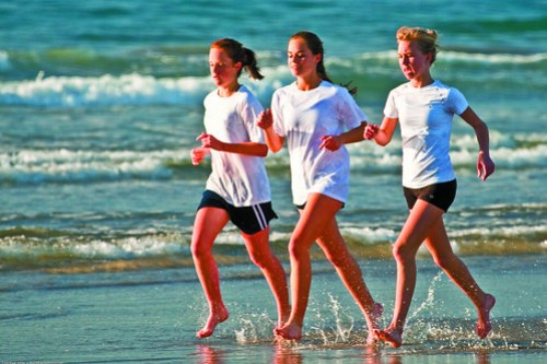 Three high school girls, as part of a larger group, run up and down the beach