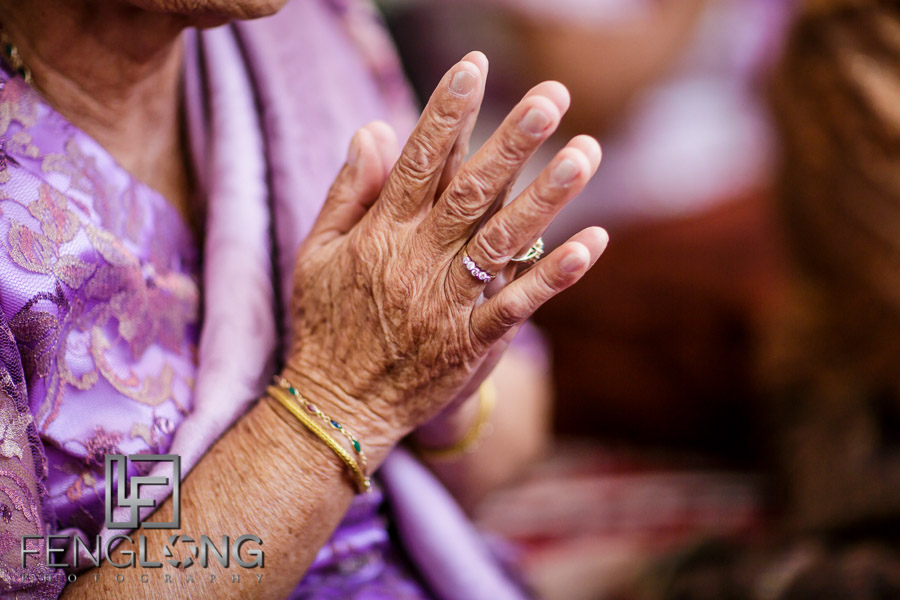 Elderly family member prays during buddhist ceremony