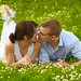 young and happy couple is kissing on a meadow