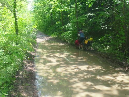 hannah pushing bike around muddy puddle
