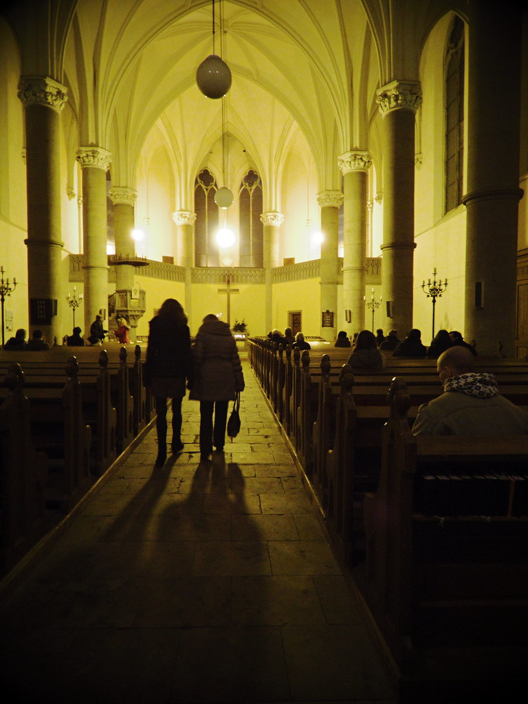 People Entering the Red Church in Brno