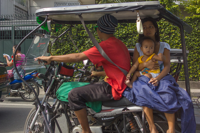 Mother and child riding a tricycle in Laguna, Philippines.