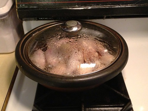 Clay pot with chicken wings on the stove