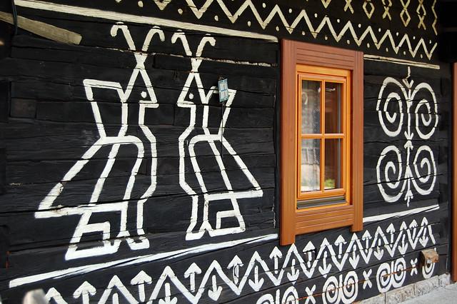 Símbolos blancos pintados en una casa de madera de Čičmany