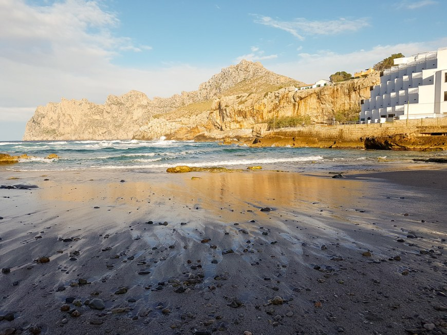 A view of the beach in Cala Sant Vicente, at sunset. The water is retreating from the beach whilst the sun warms up the mountain behind. Mallorca, Spain.