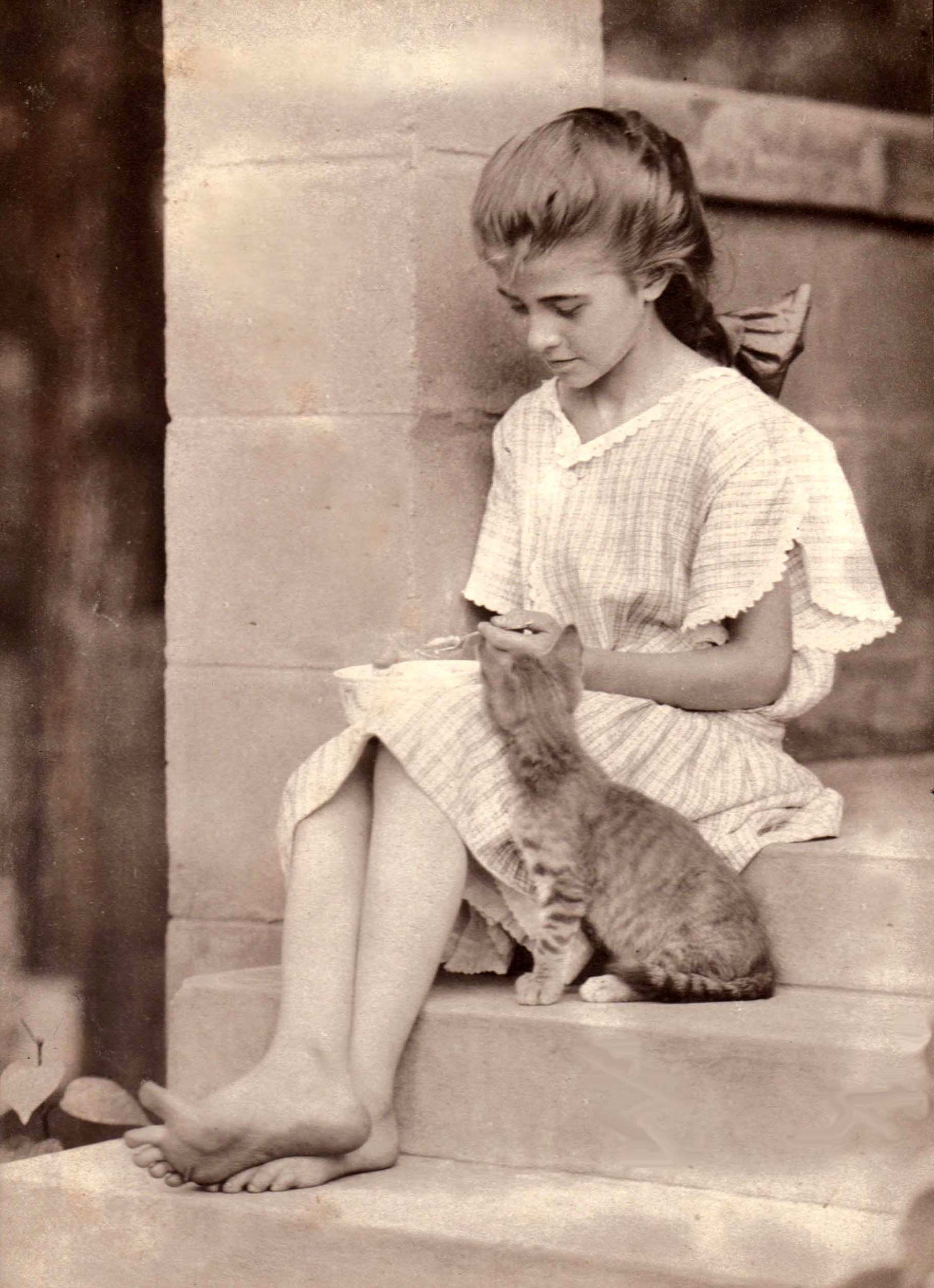 C.R. Tucker: Girl feeding a kitten, June 1908