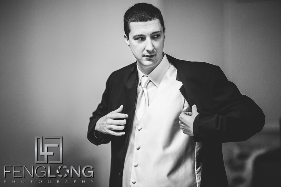 Groom puts on his suit in preparation for the wedding