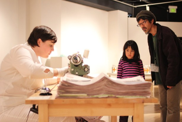 "SF State Alumni Toru Sugita (right) and Madoka Sugita (center) view artist Aimée Brown (left) sewing newspapers during her installation at the ""Progressive Proof"" printmaking gallery opening in the Fine Arts gallery in the Fine Arts Building Sat. Feb. 22. Photo by Tony Santos / Xpress"