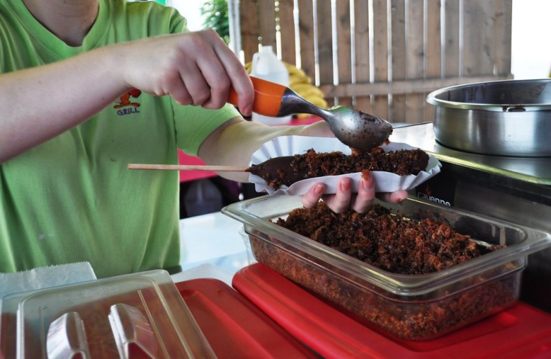 Sprinkling the Crumbled Bacon on a Chocolate-Covered Frozen Banana to Make the Baconana - Erie County Fair, Hamburg, N.Y., Aug. 10, 2014