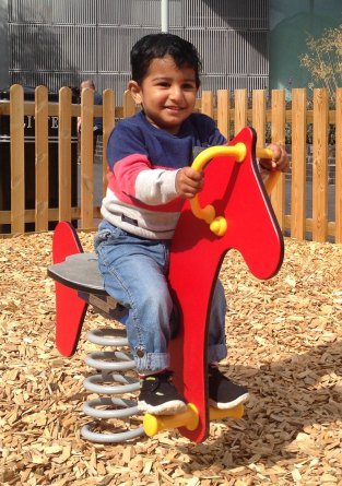 Adi riding the wooden horse